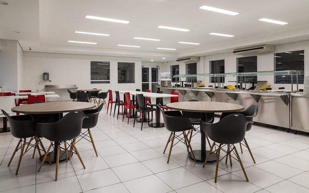 imagem de refeitório com mesas, cadeiras e local de servir comida